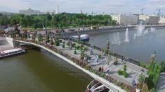 Tourists walk on Tretyakov pedestrian bridge adorned by flowers Stock Footage