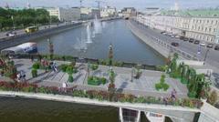 Tourists walk on Tretyakov bridge among plants in form of heart Stock Footage