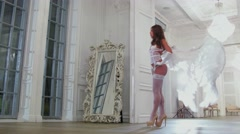 Model in white underclothes and angel wings poses near window Stock Footage