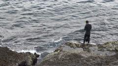4k Asian Fisherman Wearing neoprene in coast rock for practice Free Diver -Dan Stock Footage