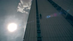 Careful male athlete descending down high house and bright sunlight Stock Footage
