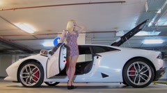 Blonde model poses near sport car in garage during photo session Stock Footage