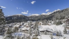 Time-lapse of snow-covered village and evergreen forest. Stock Footage