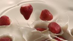 Lots of strawberries fall down in beige cream yogurt create splashes and wave Stock Footage