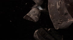 Pieces of dark brown chocolate flying in air on black background in slow motion Stock Footage