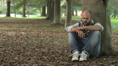 Lonely man crouched under a tree reflecting sadly Stock Footage