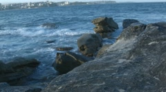 Waves breaking on rocks at Manly Beach while a ski boarder passes by. Stock Footage