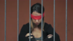 Young woman kidnapped and imprisoned in a cell, blindfolded Stock Footage
