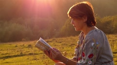 Ukrainian Woman in Embroidery Dress Reads the Book in Sun Lights at Sunset. Stock Footage