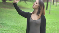 Young girl in the park shooting witty selfies Stock Footage