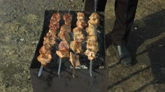 The man corrects skewers on the grill with meat - cooking barbecue. Stock Footage
