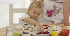 Little girl placing berries on muffins Stock Footage