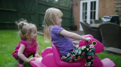 4K Toddler girl playing in the garden with older sister, on rocking toy Stock Footage