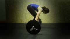 Woman athlete crossfit does the push ups with a huge barbell Stock Footage