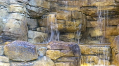 Waterfall flowing over the wall with large stones. Stock Footage