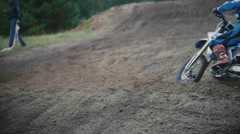 Slow motion: Motocross racer jumping. Rear view of biker on track in rapid shoot Stock Footage