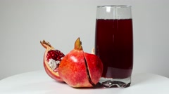 Pomegranate juice in a glass and ripe pomegranate Stock Footage