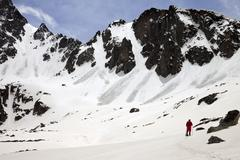 Hiker in snow mountain with trace from avalanches at sun spring day Kuvituskuvat