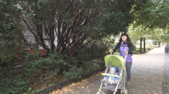 Young mother walking with her baby in city in autumn day. Stock Footage