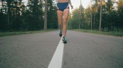 Woman running on asphalt road, super slow motion Stock Footage