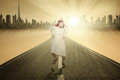 Arabian man running on the road Stock Photos