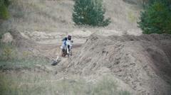Motocross racer biker in blue jumpsuit jumping on track in rapid shoot, slow Stock Footage