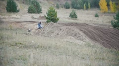 Motocross racer biker in blue jumpsuit jumping on track among the spruces in Stock Footage