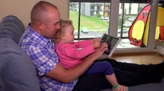 Father with his little daughter watching photos on tablet computer screen Stock Footage
