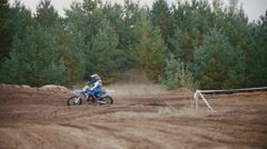 Motocross racer mxgirl on dirt bike jumping on track among rhe spruces in rapid Stock Footage