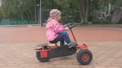 Little girl having fun driving a pedal car in autumn day. Stock Footage