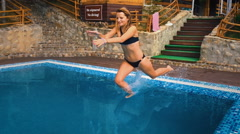 Young funny girl jumping into the pool. Slow motion. Stock Footage