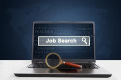 Laptop with job search text and magnifier Stock Photos