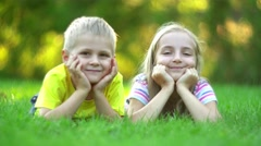 Children lying on green grass Stock Footage