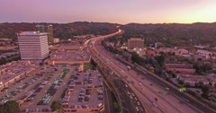 Pan across aerial view of city traffic on 405 freeway at dusk in Los Angeles Stock Footage