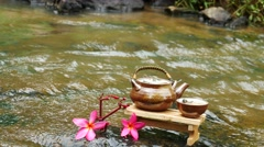 Flower plumeria or frangipani in waterfull, tea jar on wooden table, Stock Footage