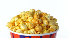 Cheese popcorn rotates on a white background. Close up shot Stock Footage