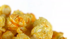 Cheese popcorn rotates on a white background. Super close up shot Stock Footage