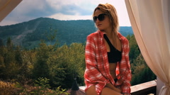 Girl in bikini straightens the hair on the background of mountains. Slow motion. Stock Footage