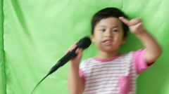 Asian little boy singing a song and dance on green background, Stock Footage