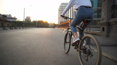 Back view female rides a bike along the empty morning street Stock Footage