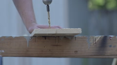 Slow Motion Large drill bit drilling through wooden board - side angle Stock Footage