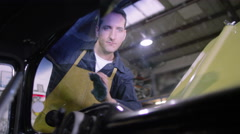 4K Male and female mechanics servicing classic car in garage workshop Stock Footage