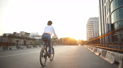 Back view woman rides bicycle down the empty street at sunrise Stock Footage
