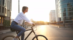 Young female riding bike through the empty morning city Stock Footage