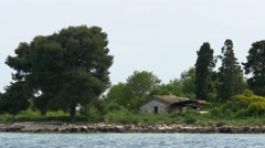 Close up of small stone cabin on green island Stock Footage
