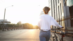 Back view woman walks down the street carrying her bike Stock Footage