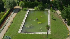 Duino castle garden pool with sculpture aerial view Stock Footage