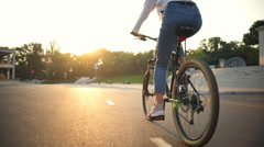 Back view young female riding a bike through the park in sunlight Stock Footage