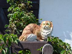 Toy cat on the fence. Statuette of a cat in plaster and plastic on the fence Stock Photos