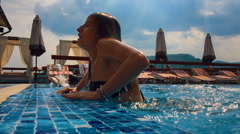 Sexy girl emerges from a pool. Slow motion. Stock Footage